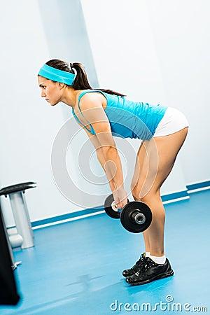 Mujer joven que hace el cuerpo-edificio en el gimnasio