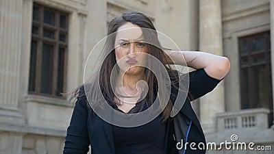 Mujer joven que hace la expresión de la cara que sacude su pelo y que da vuelta de tristeza a la felicidad almacen de metraje de vídeo
