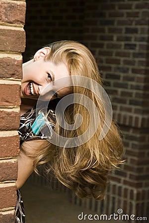 Mujer joven que oculta alrededor de esquina