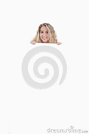 Mujer joven que oculta su carrocería detrás de un cartel en blanco