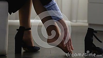 Mujer joven que saca los zapatos y que da masajes a las piernas, cansadas después todo el día de paseo almacen de video