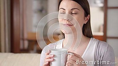 Mujer joven que se relaja en el sofá en casa Café o té de consumición bastante femenino de la taza en sala de estar metrajes