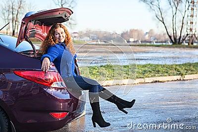 Mujer joven que se sienta en tronco de coche
