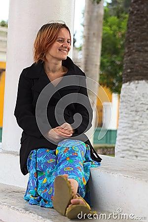 Mujer joven que se sienta en una columna