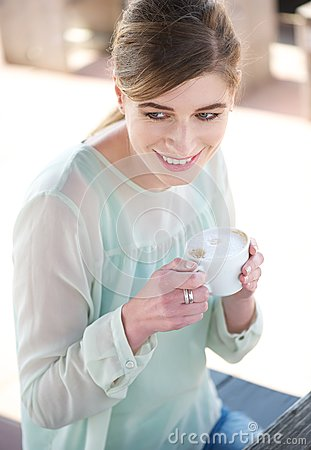 Mujer joven que sonríe y que goza de una taza de café