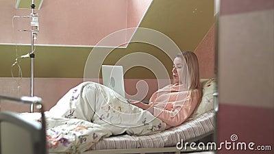 Mujer joven que usa el ordenador portátil que tiene charla video en cama de hospital almacen de metraje de vídeo