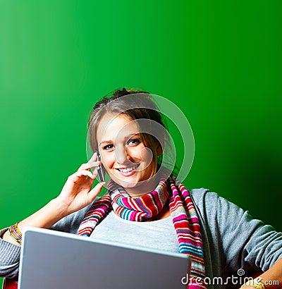 Mujer joven que usa un teléfono celular y una computadora portátil en verde