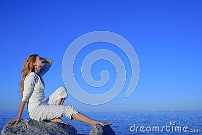 Mujer joven Relaxed que disfruta de puesta del sol por el mar