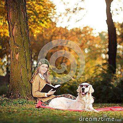 Mujer Joven Sonriente Que Se Relaja Con Su Perro Imágenes de archivo