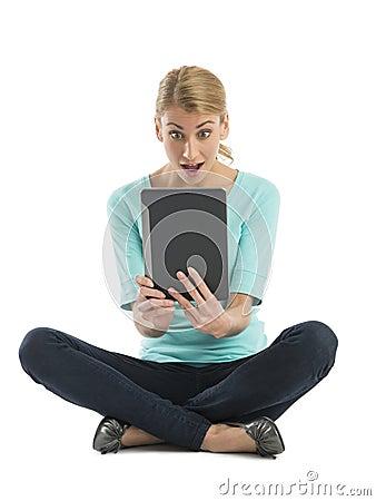 Mujer joven sorprendente que mira la tableta de Digitaces