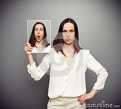Mujer joven sorprendente que oculta sus emociones
