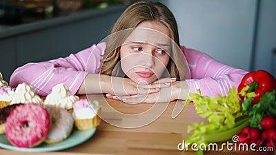 Mujer joven triste que mira en sano y la comida basura alternativamente metrajes