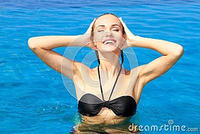 Mujer magnífica que levanta su cabeza del agua
