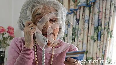 Mujer mayor que da los detalles de la tarjeta de crédito en el teléfono metrajes