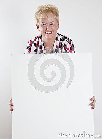 Mujer mayor que lleva a cabo una muestra blanca en blanco
