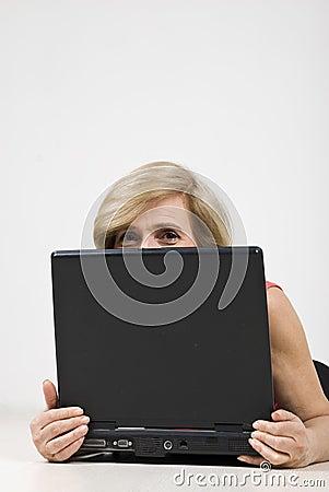 Mujer mayor que oculta detrás de la computadora portátil