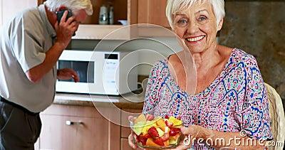 Mujer mayor que sostiene el cuenco de fruta mientras que hombre que habla en el teléfono móvil en cocina almacen de video