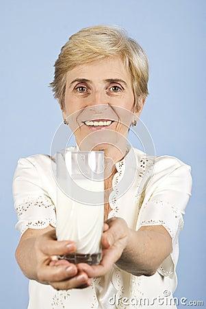 Mujer mayor sana con el vidrio de leche