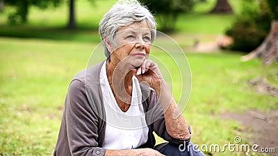 Mujer mayor trastornada que se sienta en el pensamiento del parque almacen de metraje de vídeo