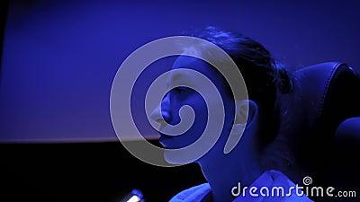 Mujer mirando alrededor en el cine con iluminación azul claro metrajes