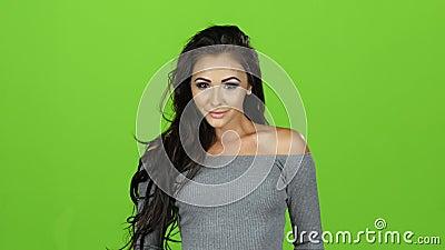 Mujer morena en el suéter gris que presenta en la cámara, pantalla verde metrajes