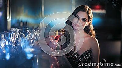 Mujer morena joven de la belleza que se sienta en la barra con el vidrio de vino en interior de lujo almacen de metraje de vídeo