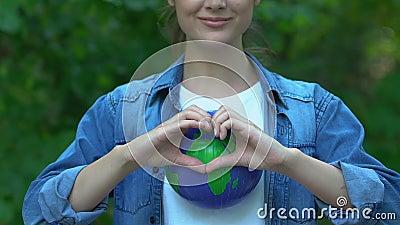 Mujer mostrando gesto de corazón en el mundo, cuidado del planeta, conciencia ambiental almacen de video