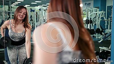 Mujer muscular del atleta que se resuelve en los pesos de elevación del gimnasio Muchacha de la aptitud que ejercita en el gimnas almacen de video