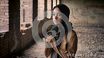 Mujer musulmán hermosa joven en el hijab negro que se coloca en el edificio abandonado y que mira la cámara con asustado y almacen de video