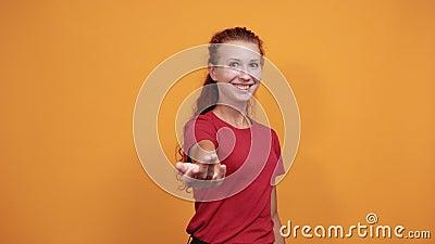 Mujer muy joven con un saludo de camisa roja, levanta la mano, sonríe almacen de metraje de vídeo