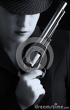 Mujer peligrosa en negro con la arma de mano de plata