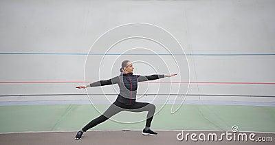 Mujer practicando yoga asana guerrera posando disfrutando de un estilo de vida saludable haciendo ejercicio al aire libre almacen de metraje de vídeo