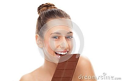 Mujer que come la barra de chocolate