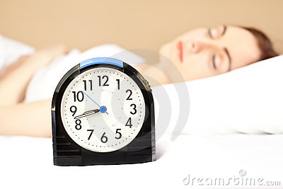 Mujer que duerme en la cama (foco en el reloj de alarma)