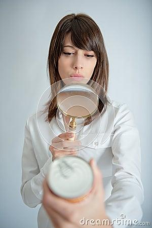 Mujer que escudriña la escritura de la etiqueta de la nutrición