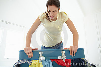Mujer que lucha para cerrar la maleta