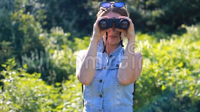 Mujer que mira a través de los prismáticos Turista de la muchacha con una mochila outdoor metrajes