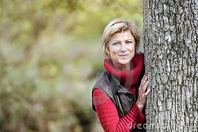 Mujer que oculta detrás de un árbol