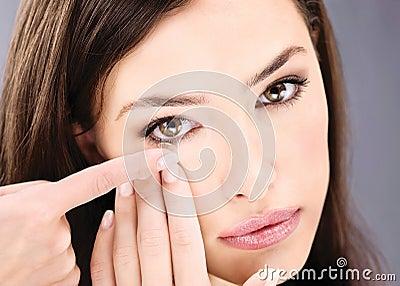 Mujer que pone la lente de contacto en su ojo