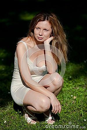 Mujer que se agacha en el parque