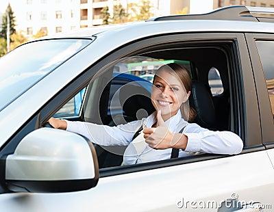 Mujer que se sienta en coche y que muestra los pulgares para arriba
