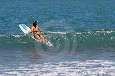 Mujer que se sienta en la tabla hawaiana