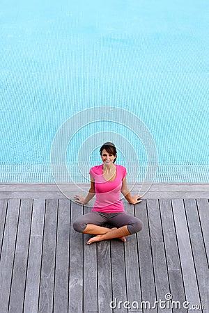 Mujer que se sienta por la piscina