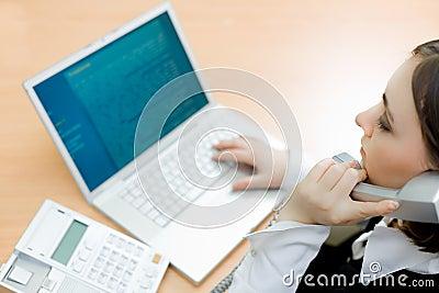 Mujer que trabaja en la computadora portátil (foco en mujer)