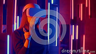 Mujer que usa auriculares VR en pendientes rápidas de lado a lado mientras juega en el espacio oscuro iluminado con luz de neón almacen de video