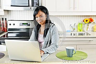 Mujer que usa el ordenador en cocina