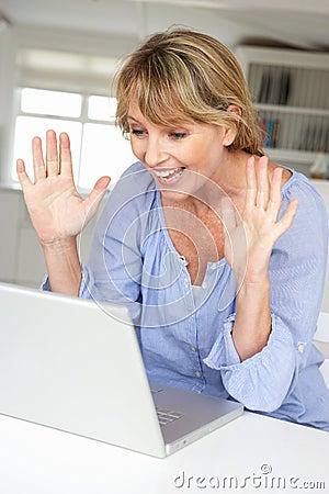 Mujer que usa la computadora portátil en webcam