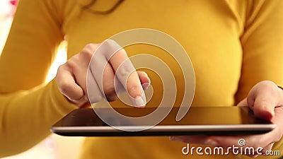 Mujer que usa la tableta digital en casa 1080i almacen de metraje de vídeo