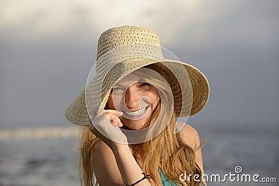 Mujer rubia con el sunhat en la playa