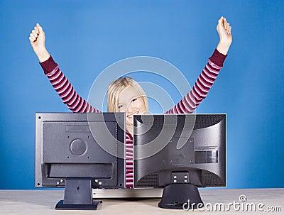 Mujer rubia joven feliz en las dos pantallas de ordenador
